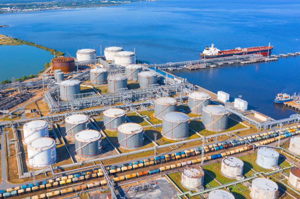 Aerial view of large fuel storage tanks at oil refinery industrial zone in the cargo seaport, and ship tanker at unloading.